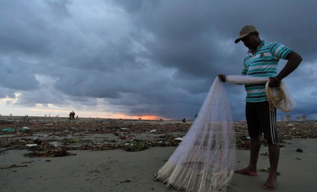 A fisherman arranges his nets as monsoon clouds hover over the Kochi beach in Kerala...