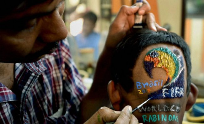 A football fan prepares for FIFA World Cup with a special hair-cut, in Howrah on Friday...