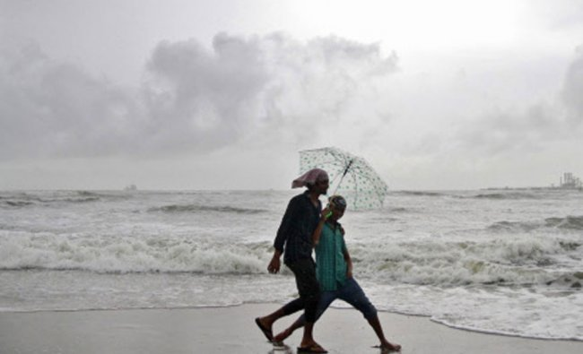 Beachgoers react to the camera while holding an umbrella as it drizzles at Kochi beach...