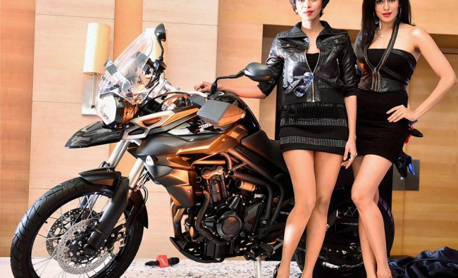 Models pose with a Triumph motorcycle during its launch in Chennai ...