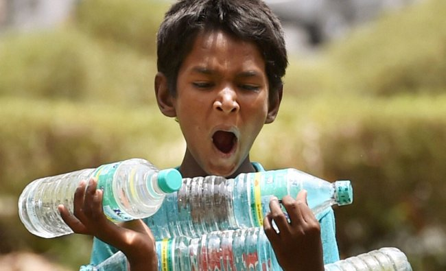 A child carrying water bottles to sell on a hot day near Rajpath in New Delhi ...