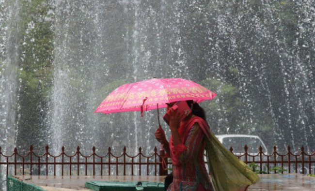 A girl, holding an umbrella, walks past a fountain on a hot day in Jammu...
