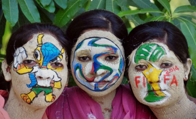 Girls paint their faces as the FIFA World Cup 2014 is scheduled to start from next week, in...
