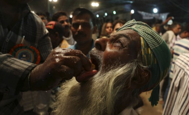 A member of the Goud family administers fish medicine to an asthma patient in Hyderabad, Sunday...