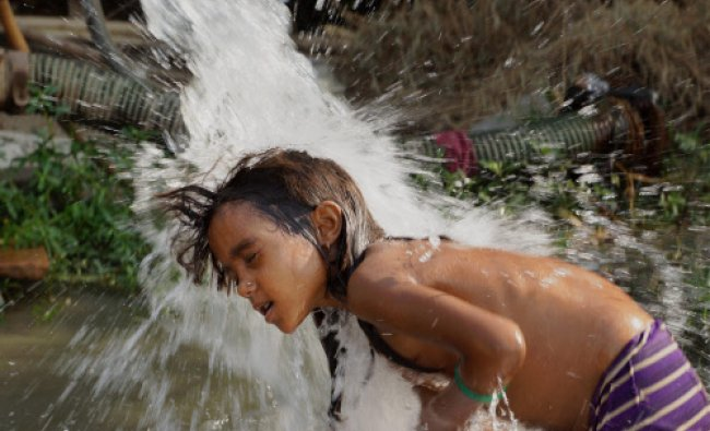 A girl takes shower under a tube well to beat the heat as mercury soars in New Delhi on Sunday....