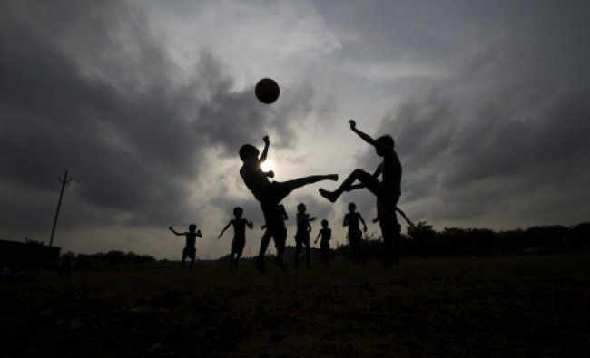 Children play soccer at a playground in Bhubaneswar, Sunday, June 8, 2014. Soccer fans around the...