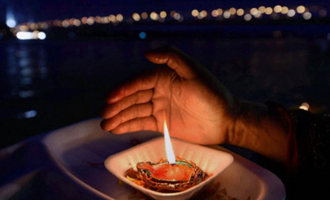 A devotee lighting a lamp during \'Ganga Puja\' at the river Hoogly in Kolkata...
