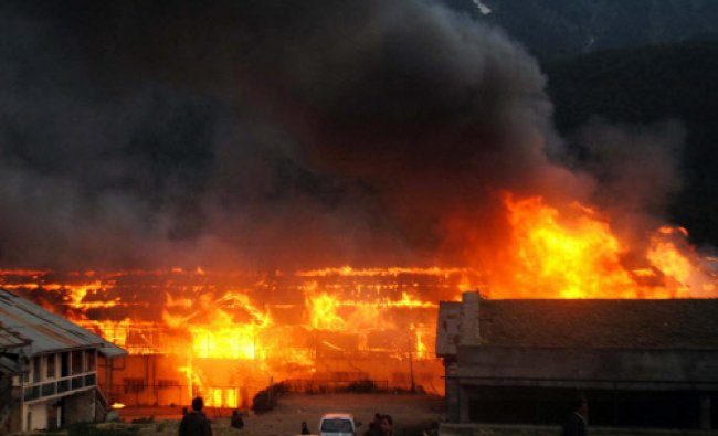 Flames raises from hotels and shops during a major fire in which dozens of hotels and shopping...