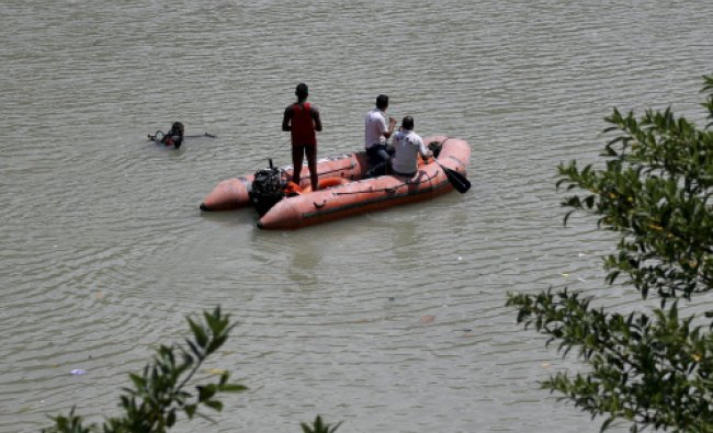 Rescuers search the Beas River after dozens of students were swept away when a dam released a...