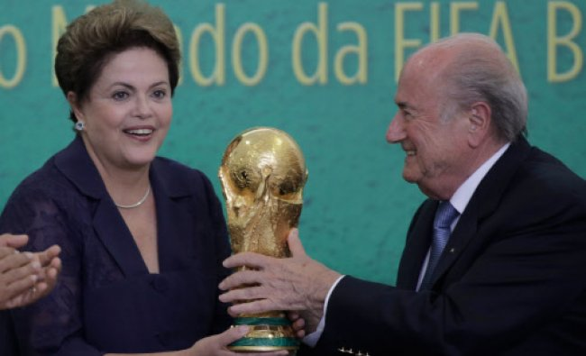 FIFA President Sepp Blatter, right, presents the 2014 World Cup trophy to Brazil\'s President...