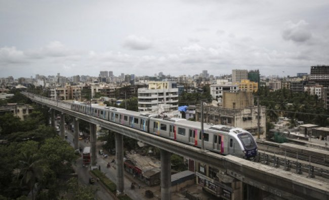 A metro train travels through a residential area in Mumbai June 9, 2014. Picture taken June 9...