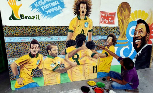 An artist paints images of Brazilian footballers at a wall...