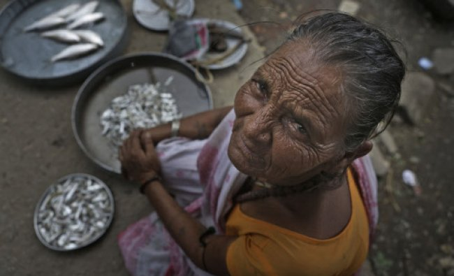 A woman, Guljeria, 75, who makes a living selling fish near the River Brahmaputra looks into the...