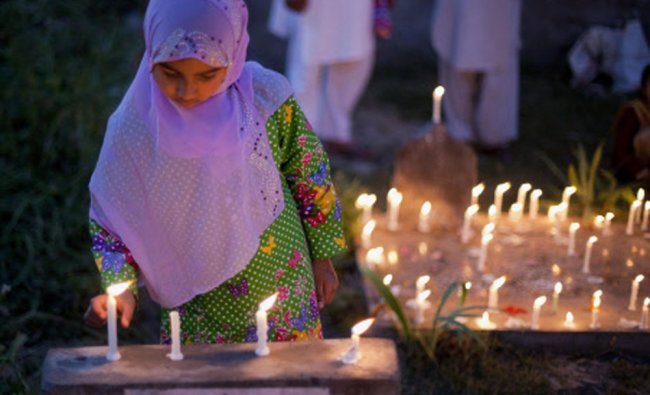 A Kashmiri Shiite girl lights a candle near the illuminated graves of relatives during Shab-e...