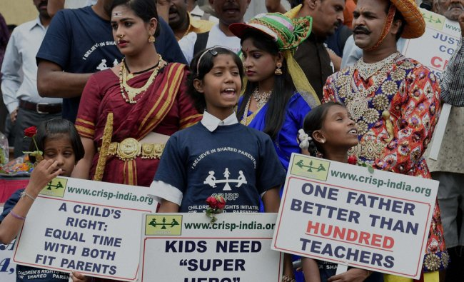 Children hold placards at outside the family court on the eve of \'Father\'s Day\' in Bengaluru ...