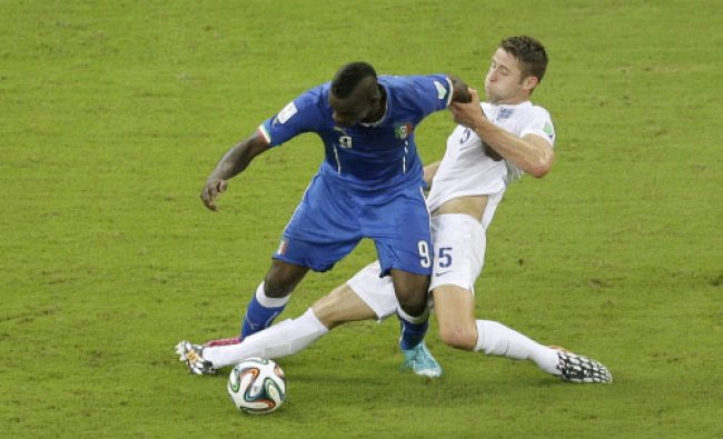 Italy\'s Mario Balotelli, left, challenges for the ball with England\'s Gary Cahill during the ...