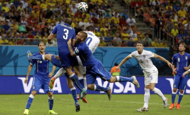 England and Italy players contest a high ball during the group D World Cup soccer match...