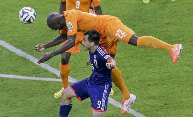 Japan\'s Shinji Okazaki, bottom, and Ivory Coast\'s Sol Bamba challenge for the ball during ...