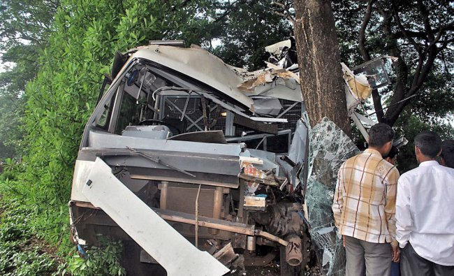 People looking at the damaged bus that hit a roadside tree at village Koparde in Kolhapur ...