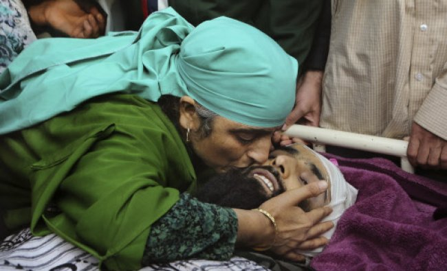 The mother of Adil Ahmed Mir, a suspected rebel, kisses his face during a funeral procession in...
