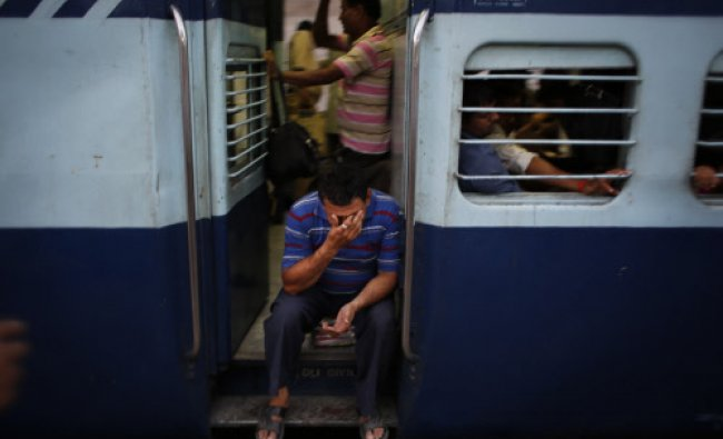 A man sits at the gate of a coach of a moving train in New Delhi, India, Friday, June 20, 2014...