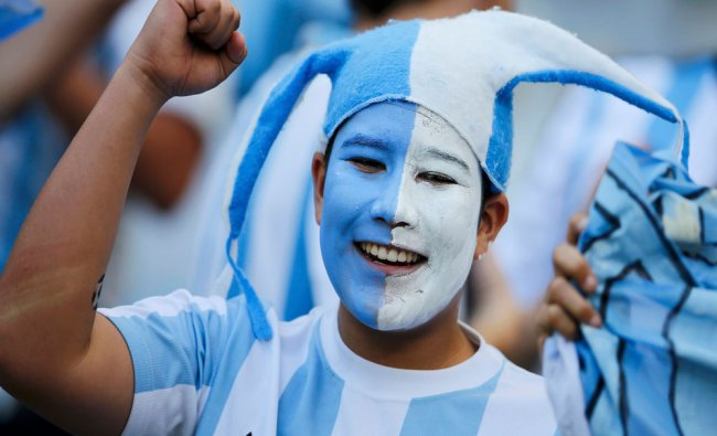 An Argentina fan cheers before the 2014 World Cup Group F soccer match between Argentina and ...