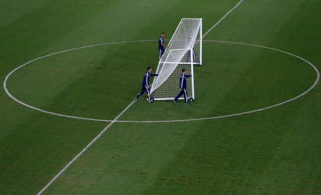 Bosnian national soccer coach Safet Susic, accompanied by assistants, move a goalpost during a ...