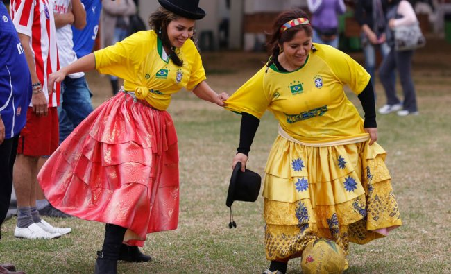 Andean women wearing Brazil-themed jerseys play soccer at a market in Lima June 20, 2014. As the...