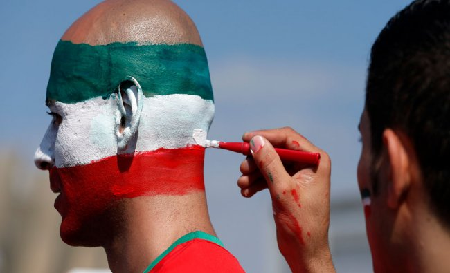 An Iranian fan has his head painted in the national colours ahead of the group F World Cup soccer...