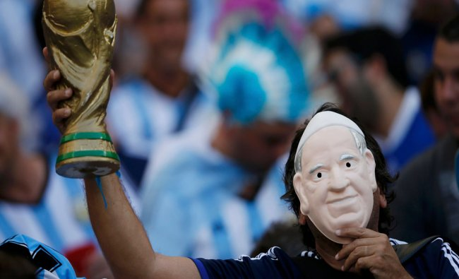 A fan holds a Pope Francis mask to his face as he waits for the start of their 2014 World Cup ...