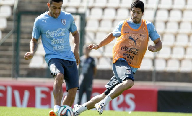 Walter Gargano, and Luis Suarez, right, of a Uruguay\'s national team runs for the ball during a...