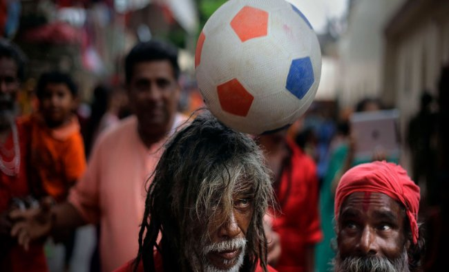 A Sadhu, balances a ball on his head as others watch at the Kamakhya temple in Gauhati, Saturday...