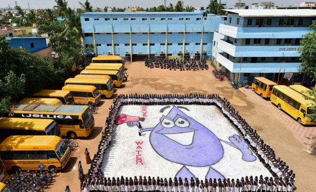 Students stage a concept drawing to encourage rainwater harvesting among people, in Chennai on...