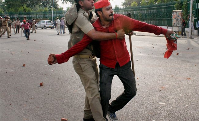 A policeman grabs a Samajwadi Party worker who was pelting bricks at BJP office during a vioent...
