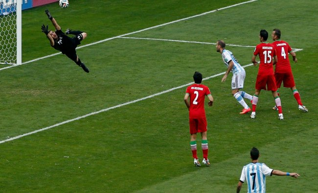 Iran\'s goalkeeper Alireza Haghighi fails to save a goal by Argentina\'s Lionel Messi (unseen)...
