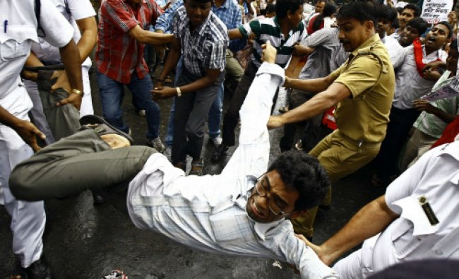 A police personnel scuffle with an activist of the Socialist Unity Centre of India (SUCI) during...