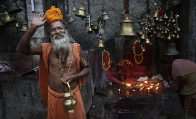 A sadhu waves to the camera at the Kamakhya temple in Gauhati, Saturday, June 21, 2014. The...