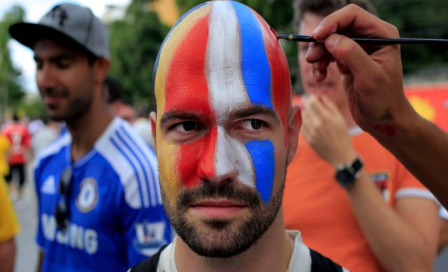 A soccer supporter gets his face painted with Belgium and Russia national color flags outside...