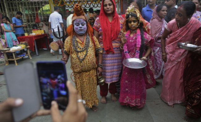A devotee takes photographs on his mobile phone as his wife poses with a man dressed as god Shiva...