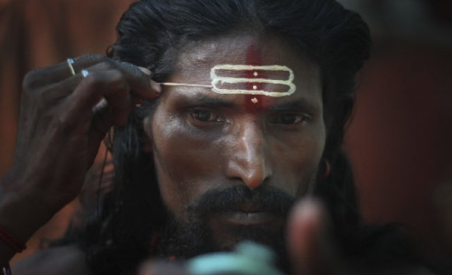 A holy man applies sandalwood paste on his forehead looking at a mirror during the Ambubasi...