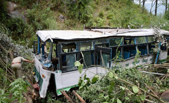 A policeman inspects a bus which fell into a deep gorge at a village near Mandi...