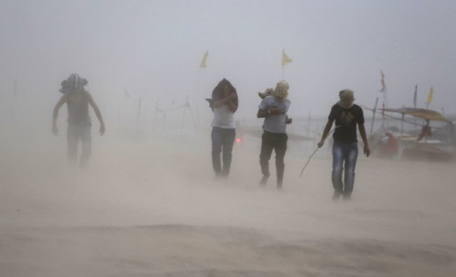 People walk during a dust storm on the banks of Sangam, the confluence of rivers the Ganges and...