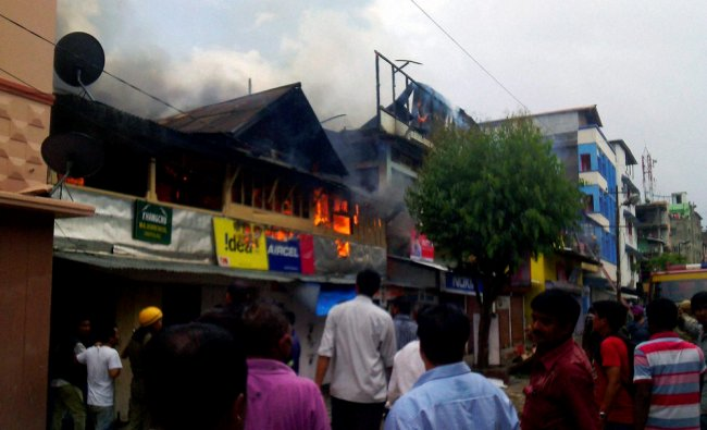 Fire personnel dousing a fire that broke out in a commercial area in Imphal ...