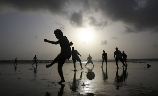Youth play soccer on the Arabian Sea shore in Mumbai, Tuesday, June 24, 2014. In a country where...