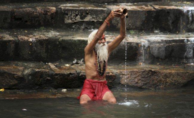 A holy man performs rituals at a pond at the Kamakhya Hindu temple during the Ambubasi festival...