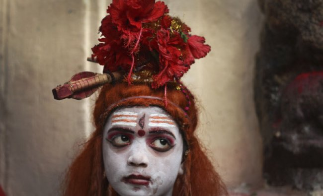 Sumanta Das, a ten year old Indian boy dressed like Shiva takes rest in between seeking alms at...