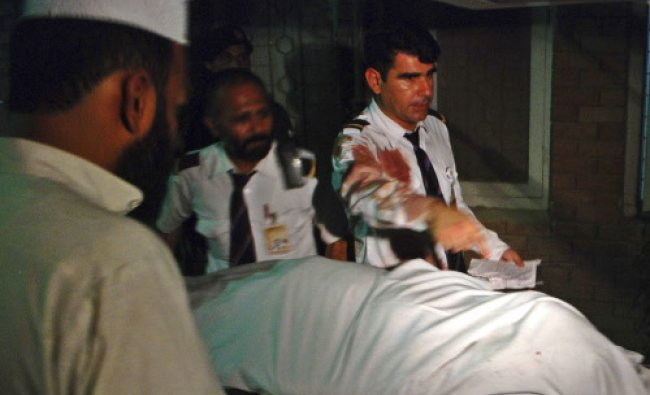 Crew members of a Pakistan International Airlines(PIA) plane are seen beside the body of a woman...