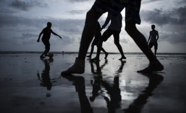 People are silhouetted as they play soccer at a beach along the Arabian Sea in Mumbai June...