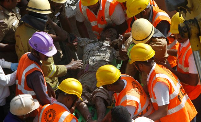 Rescue workers carry body of a victim at the site of a collapsed 11-storey building in Chennai ...