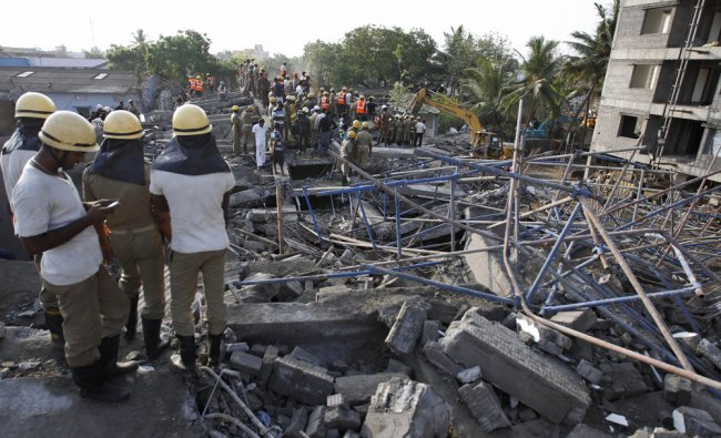 Rescuers search amid the rubble of a building that collapsed late Saturday in Chennai ...